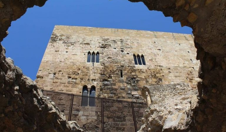 Uns operaris foraden la Muralla romana de Tarragona del segle II per col·locar una bastida